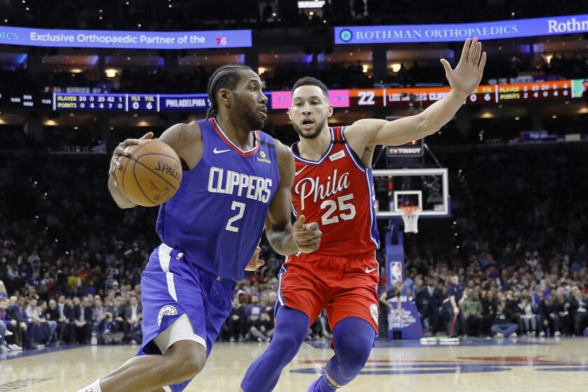 The Clippers' Kawhi Leonard drives past Philadelphia's Ben Simmons during the first half Tuesday in Philadelphia.