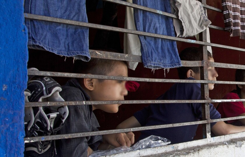 "Children watch through a barred window inside ""La Gran Familia"" (The great family) shelter, where police earlier this week rescued almost 600 people, including 458 children in Zamora, Mexico."