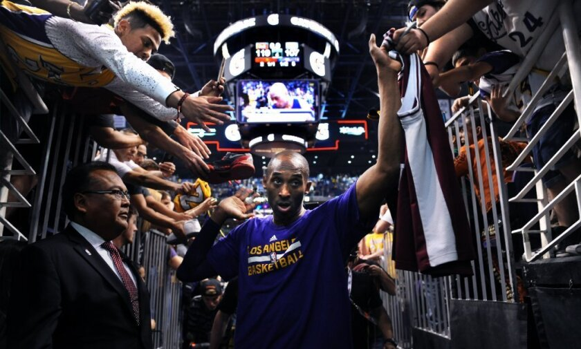 Kobe Bryant high-fives fans as he walks off the court for the last time in Phoenix after a game against the Suns on March 23.