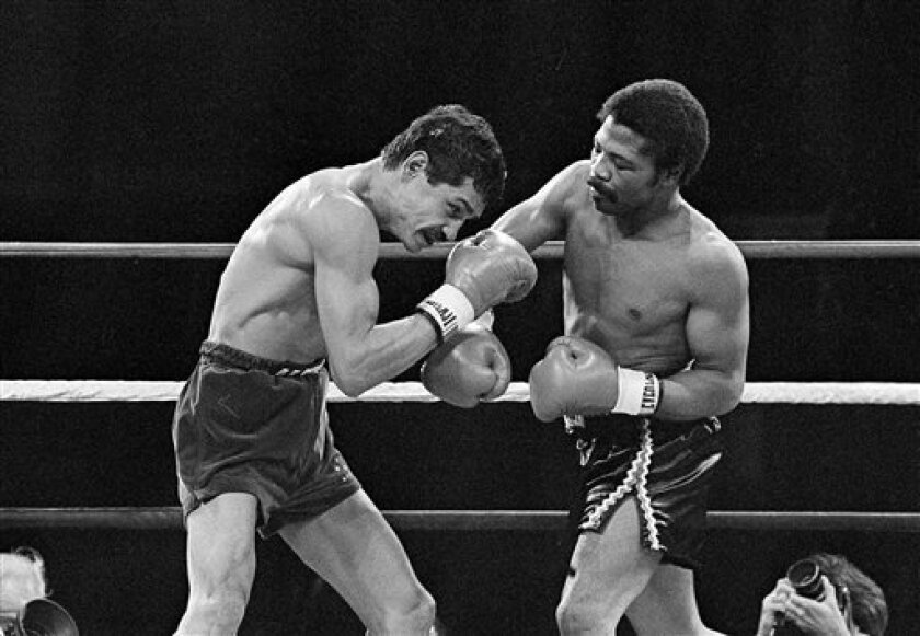 FILE - In this Nov. 12, 1982 file photo, Alexis Arguello covers up as defending champ Aaron Pryor throws a hard right during the second round of boxing action at the Orange Bowl in Miami.Nearly three decades ago, a ferocious puncher and brilliant ring tactician waged one of boxing's epic brawls under the twinkling lights of the Orange Bowl in Miami, a fight so big that few remember Roberto Duran was the walk-out bout. (AP Photo, File)