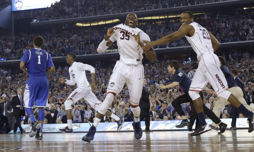 Connecticut players including center Amida Brimah (35) and guard Lasan Kromah (20) celebrate as Kentucky guard James Young (1) leaves the court at the end of the NCAA Tournament college basketball championship game last year in Arlington, Texas. Connecticut won 60-54.