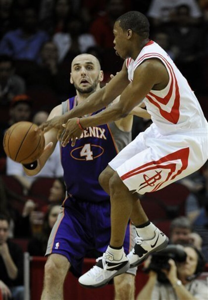 Houston Rockets' Kyle Lowry, right, passes the ball around Phoenix Suns' Marcin Gortat (4) in the first half of an NBA basketball game Friday, Feb. 3, 2012, in Houston. (AP Photo/Pat Sullivan)