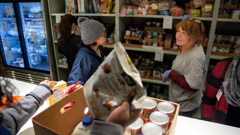 Volunteers Isabel Carmona, left, and Terri Silverstone help a Transportation Security Administration employee pick out groceries at the Lakeview Pantry Monday in Chicago. As the partial government shutdown drags on, federal employees in Illinois are turning to food pantries.