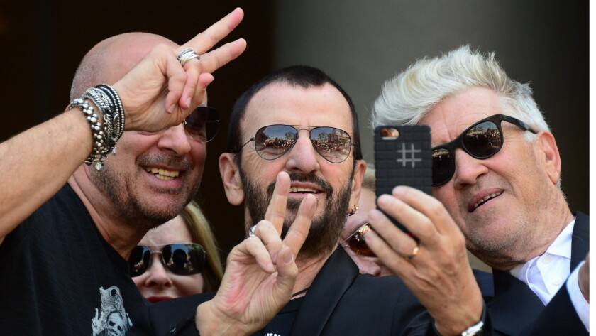 Ringo Starr takes a selfie while joined by fashion designer John Varvatos, left, wife Barbara Bach, rear, and filmmaker David Lynch, right, in Hollywood in 2014 on his 74th birthday.
