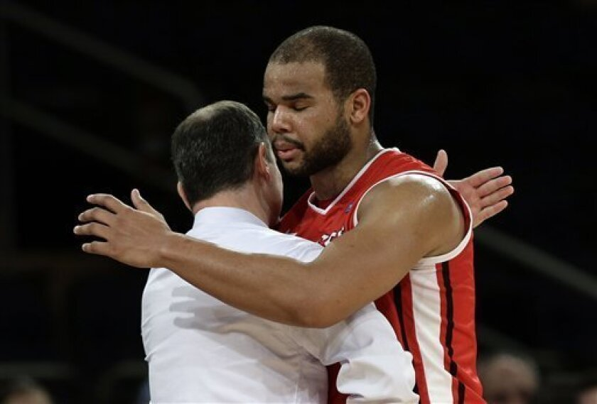Rutgers' Austin Johnson hugs head coach Mike Rice during the second half of an NCAA college basketball game against Notre Dame at the Big East Conference tournament, Wednesday, March 13, 2013, in New York. Notre Dame won 69-61. (AP Photo/Frank Franklin II)