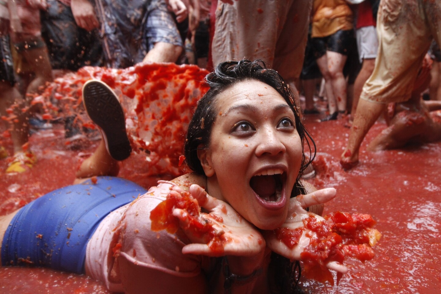 A participant in La Tomatina lies in a pool of tomatoes.