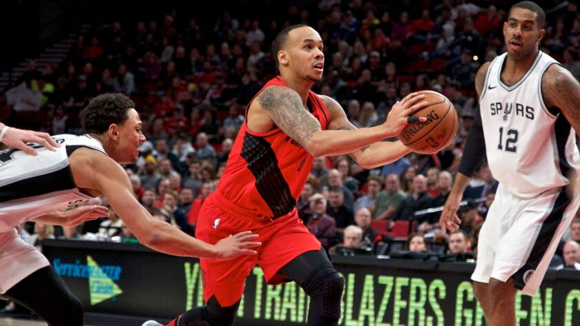 Portland Trail Blazers guard Shabazz Napier dribbles past San Antonio Spurs guard Bryn Forbes and San Antonio Spurs forward LaMarcus Aldridge during the first half.