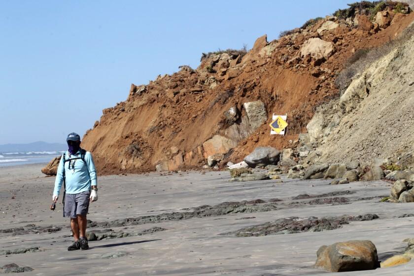 Un hombre pasa por una sección del acantilado costero que se derrumbó en Del Mar
