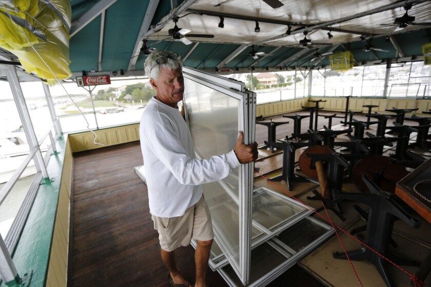 Bob Wilder, an employee at Morgan Creek Grill, moves windows from the third floor bar at the popular restaurant on the Isle of Palms, S.C., Wednesday in advance of Hurricane Matthew.
