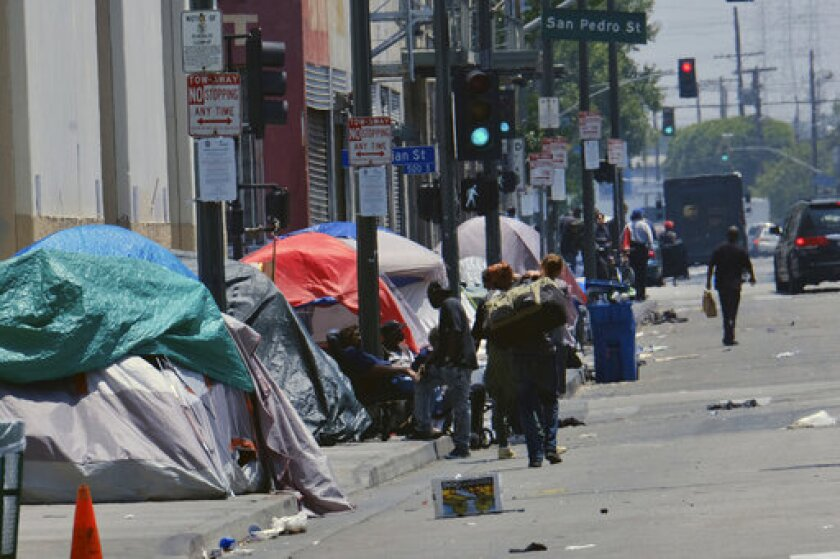 FILE - In this May 30, 2019 file photo, tents housing homeless line a street in downtown Los Angeles. A proposal to restrict where homeless people may camp around Los Angeles drew protest at a City Council meeting from demonstrators who fear the rules would criminalize homelessness. Council members began discussion Tuesday, Sept. 24, 2019, on proposed changes to the city's code that would prevent people from sleeping near sensitive areas such as schools, or blocking right-of-ways like driveways and loading docks. (AP Photo/Richard Vogel, File)