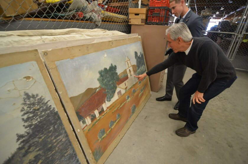 Oceanside Deputy Mayor Chuck Lowery and City Clerk Zack Beck inspect about 20 paintings the city has had in storage since the 1980s.