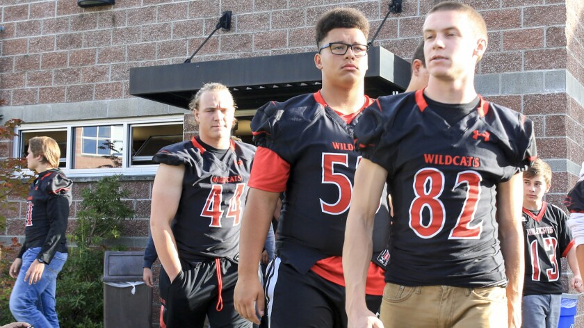 Members of the Archbishop Murphy football team leave a news conference on Oct. 5, 2016, after another school refused to play them.