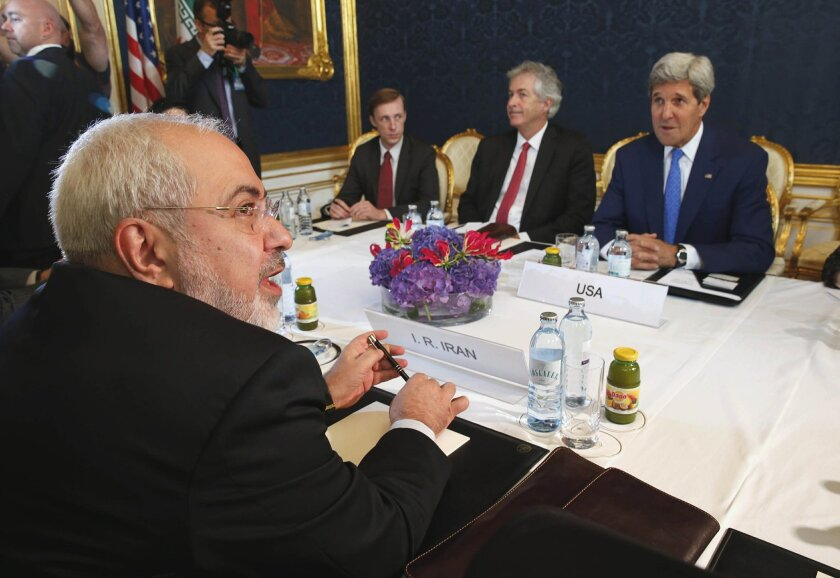 Iran's Foreign Minister Javad Zarif, foreground, holds a bilateral meeting with US Secretary of State John Kerry background right, on the second straight day of talks, in Vienna, Austria, Monday July 14, 2014. Secretary of State John Kerry continued in-depth discussions Monday with Iran's top diplomat in a bid to advance faltering nuclear negotiations, with a deadline just days away for a comprehensive agreement. (AP Photo/Jim Bourg, Pool)