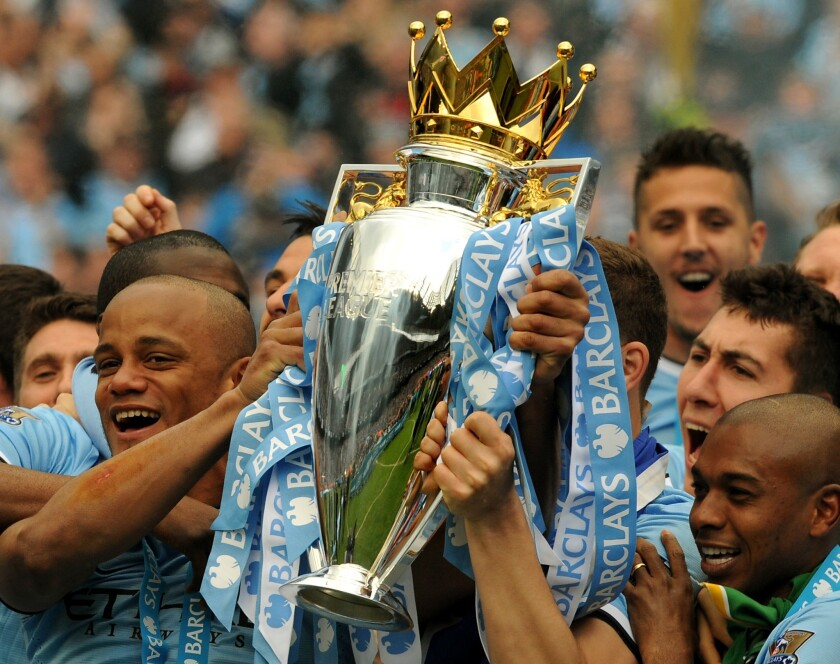 Manchester City's Vincent Kompany celebrates with the Premier League trophy after clinching the team's second title in three years with a 2-0 win Sunday over West Ham United.