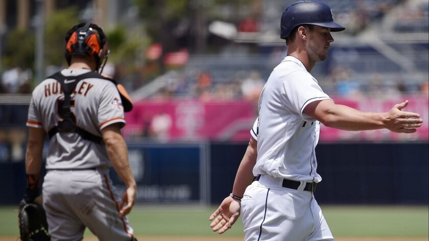 The Padres' Wil Myers, right, celebrates after scoring a run on an RBI double by Eric Hosmer as San Francisco Giants catcher Nick Hundley looks on during the first inning of game at Petco Park.