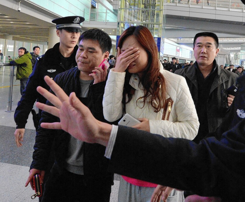A woman at Beijing Capital International Airport reacts to the news that a Malaysia Airlines flight with 239 people aboard was missing.