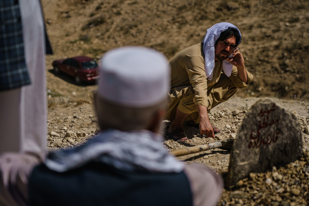 A man kneels by a grave during a funeral.