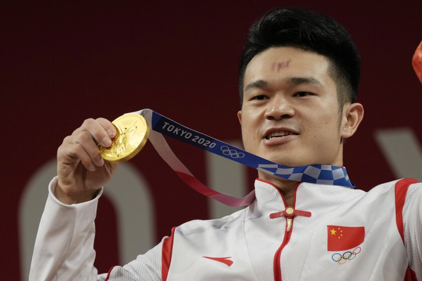 Shi Zhiyong of China celebrates on the podium after winning the gold medal in the men's 73kg weightlifting event, at the 2020 Summer Olympics, Wednesday, July 28, 2021, in Tokyo, Japan. (AP Photo/Luca Bruno)
