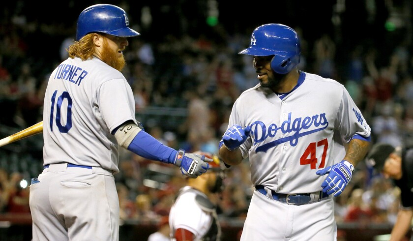 Los Angeles Dodgers' Howie Kendrick, right, greets teammate Justin Turner after hitting a solo home run against the Arizona Diamondbacks during the 10th inning on Tuesday.
