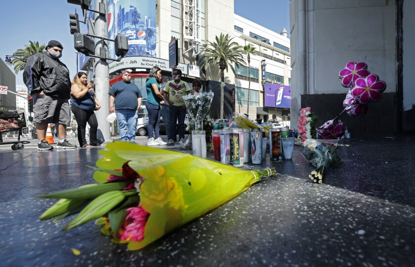 Flowers and candles mark a sidewalk memorial in Hollywood
