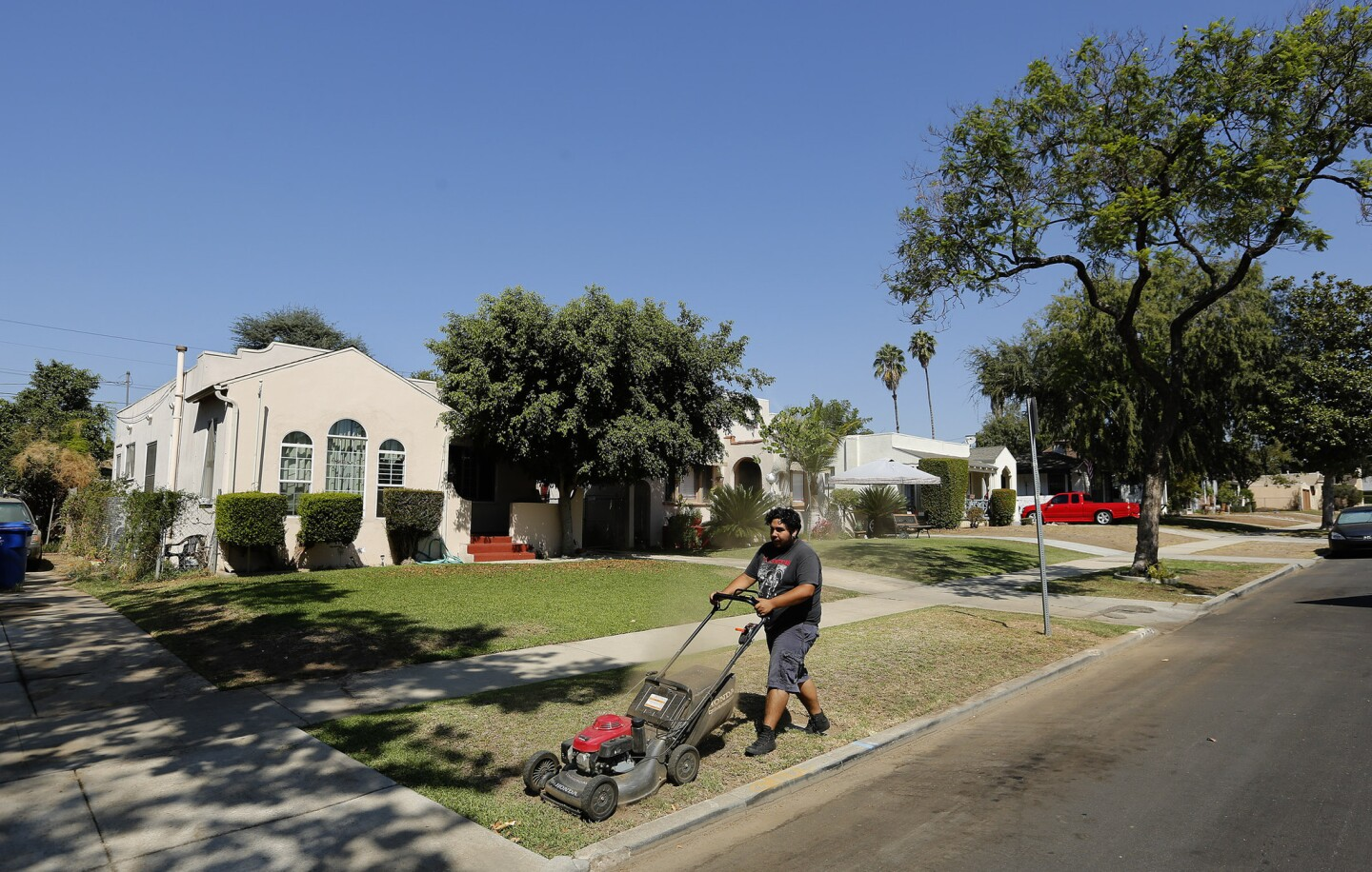 Gardener Leo Munguia mows the front lawn of a home on Sheffield Avenue in El Sereno that is owned by Caltrans. It is one of many properties purchased by the agency in the 1950s and '60s in anticipation of the 710 Freeway extension, which was never finished.