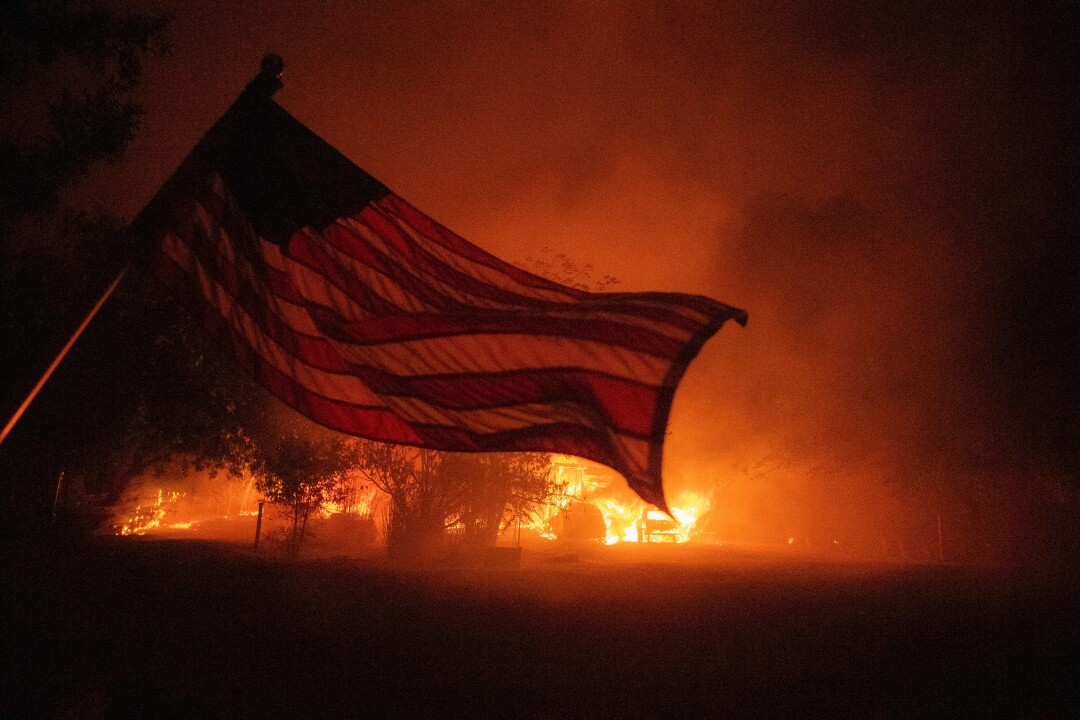 An American flag blows in front of a burning home in Vacaville, Calif.