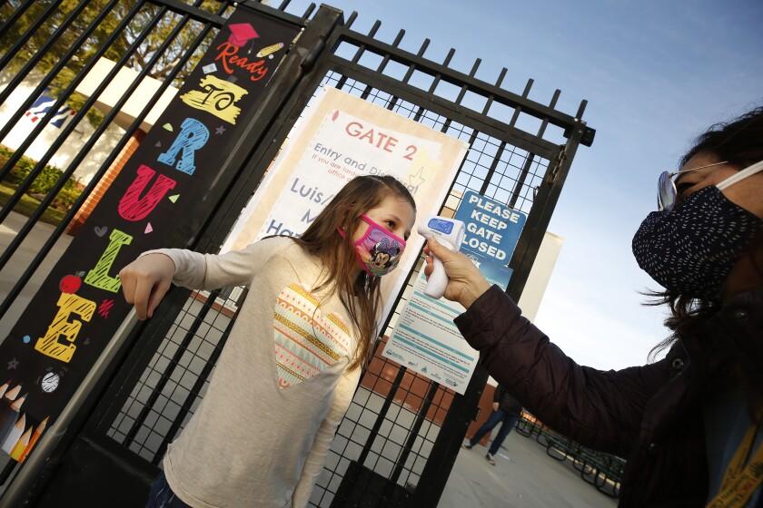 First-grader Braylen Coleman has her temperature taken by teacher's aide Firoozeh Borjian.
