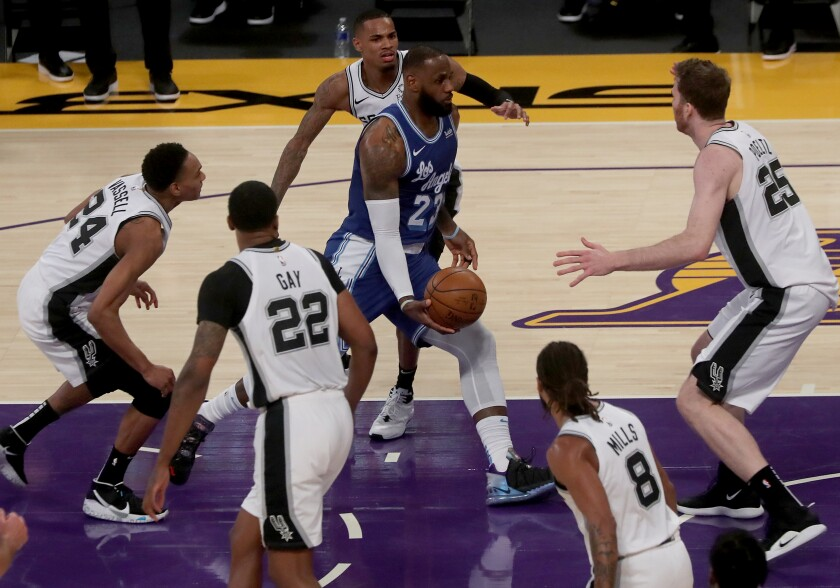 Lakers forward LeBron James draws the entire Spurs defense during a drive down the lane Thursday night.