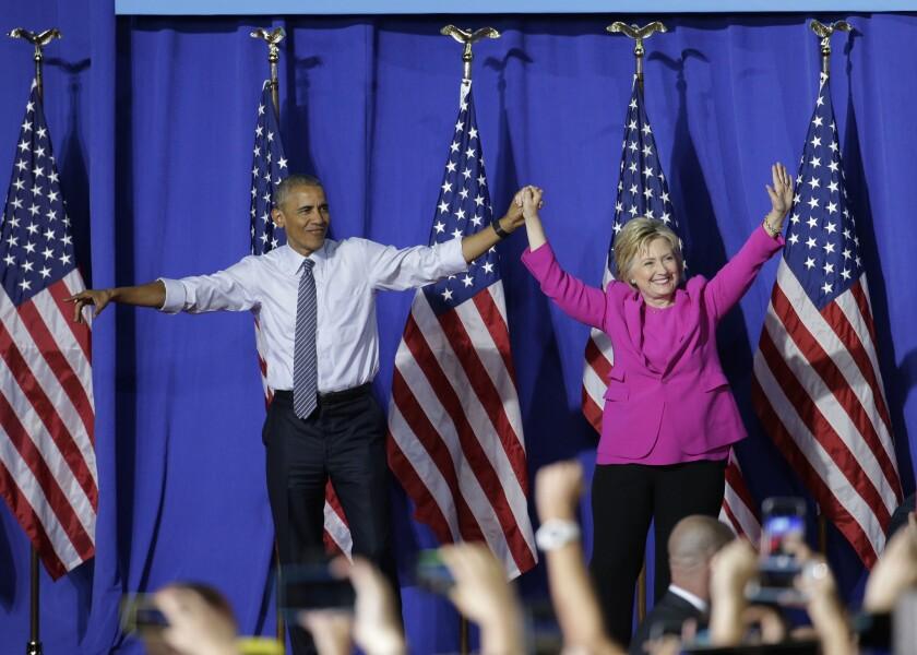 El presidente Barack Obama y la precandidata demócrata a la presidencia Hillary Clinton saludan a la multitud durante un acto de campaña en Charlotte, North Carolina, el martes 5 de julio de 2016. (AP Foto/Chuck Burton)