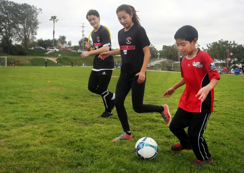 Champions League player Sean Suarez, 8, right, practices with buddies Mikey Lothringer, 16, and Julia Honda, 15, Saturday at Ada Harris Elementary School in Cardiff. The new soccer program is designed for children with special needs.