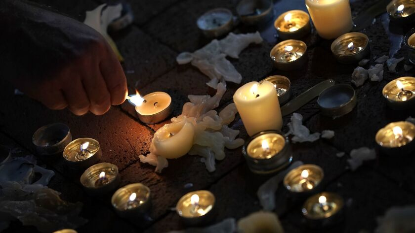 A man tends a candle at a vigil for those who died and were injured when a car plowed into a crowd of anti-racist counter-demonstrators in Virginia.