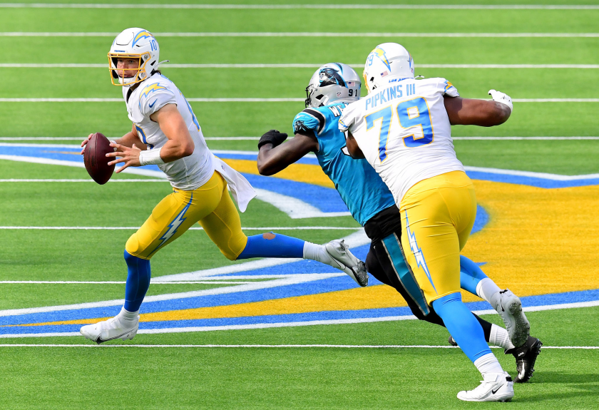 Chargers quarterback Justin Herbert rolls out of the pocket during last week's loss to the Carolina Panthers.
