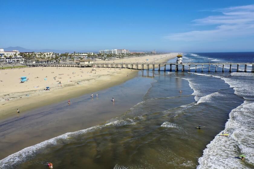 La gente disfruta de la temperatura veraniega el miércoles cerca del muelle cerrado de Huntington Beach. Se esperaba una multitud mucho mayor este fin de semana en el condado de Orange, pero no en el condado de Los Ángeles, que mantiene sus playas cerradas.