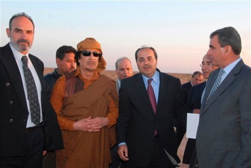 In this April 25, 2010 photo made available by the Al Arab news website Wednesday, March 2, 2011, Libyan leader Moammar Gadhafi, center left, stands with Israeli Arab lawmaker Ahmad Tibi, center right, in Serte, Libya. Israeli-Arab leaders are on the defensive over a much-publicized visit to Libya last year, where they fawned over Moammar Gadhafi and posed for a series of photographs beaming alongside the iron-fisted ruler. (AP Photo/Al-Arab, HO) NO SALES