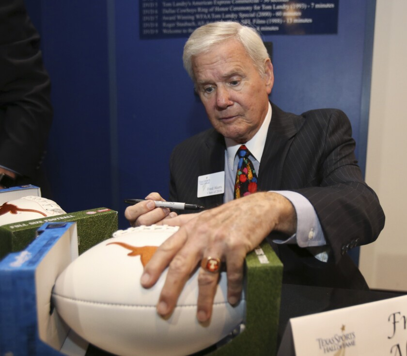 FILE - In this Feb. 2, 2016, file photo, former Texas football coach Fred Akers autographs a football during the Texas Sports Hall of Fame induction class news conference in Waco, Texas. Akers died Monday, Dec. 7, 2020, at age 82, his family said. Akers twice led the Longhorns to undefeated regular seasons before Cotton Bowl losses each time denied Texas a chance for a national championship. (Jerry Larson/Waco Tribune Herald, via AP, File)