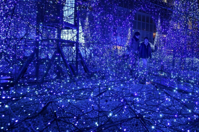 """In this Thursday, Nov. 26, 2015 file photo, a couple walks through the annual yearend illumination """"Canyon d'Azur"""" in Tokyo's Shiodome district. (AP Photo/Shizuo Kambayashi, File)"""