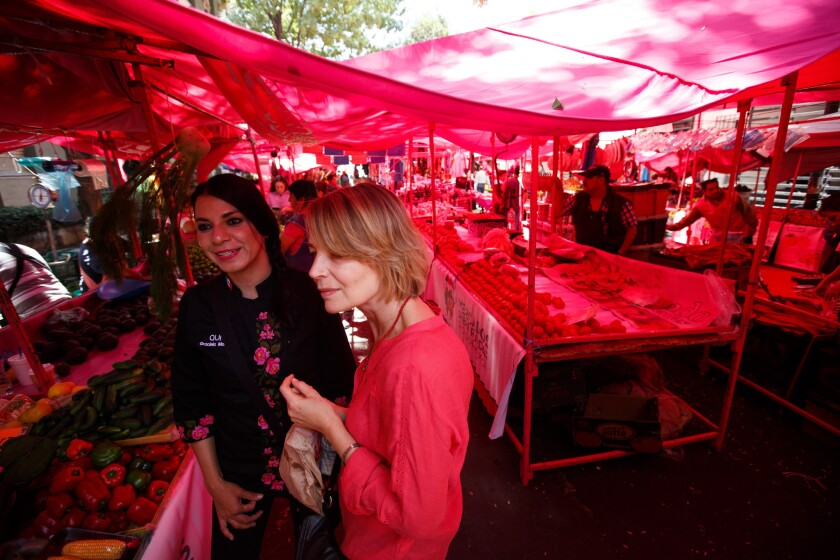 One way to explore a city is through its food. In Mexico City, Graciela Montaño, left, leads Liz Elliot on a tour of a traditional open-air market as part of an Aura Club de Maridaje tour.