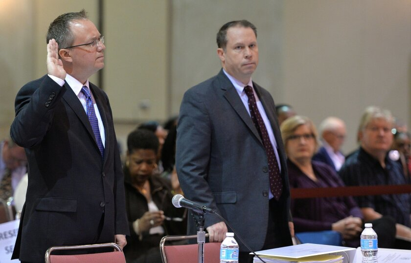 Jim Fisker-Andersen, left, director of ship services for TOTE Services, is sworn in at the beginning of his testimony at the hearings into the sinking of the El Faro on Friday, Feb. 19, 2016 in Jacksonville, Fla.  All 33 aboard died after the vessel lost propulsion and was mauled by the winds of Hu
