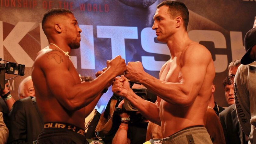 Anthony Joshua, left, and Wladimir Klitschko tap fists during the weigh-in Friday for their IBF and WBA title bout at Wembley Stadium.