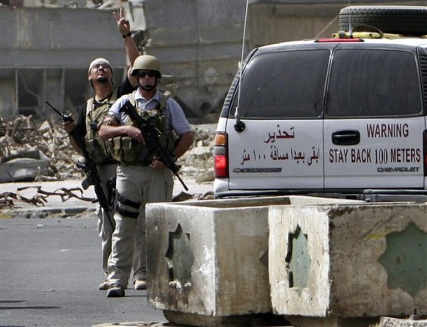 FILE - In this Tuesday, July. 5, 2005, file photo, a private contractor gestures to their colleagues flying over in a helicopter as they secure the scene of a roadside bomb attack in Baghdad, Iraq.  (AP Photo/Khalid Mohammed, File)