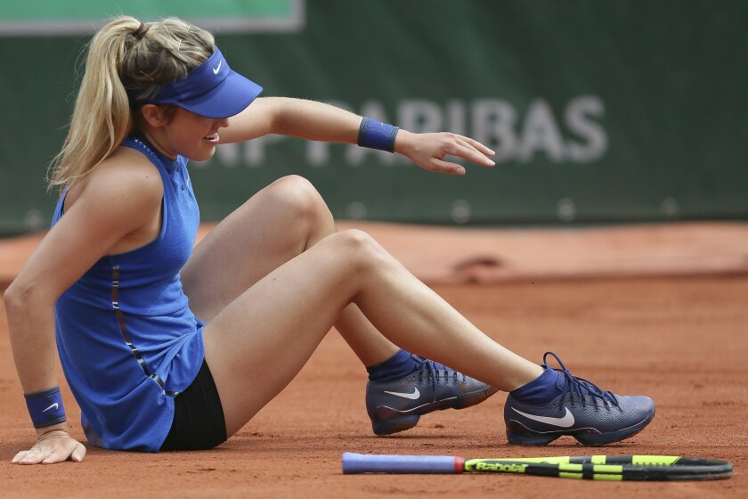 Canada's Eugenie Bouchard slips and falls in her second round match of the French Open tennis tournament against Timea Bacsinszky of Switzerland at the Roland Garros stadium in Paris, France, Thursday, May 26, 2016. (AP Photo/David Vincent)