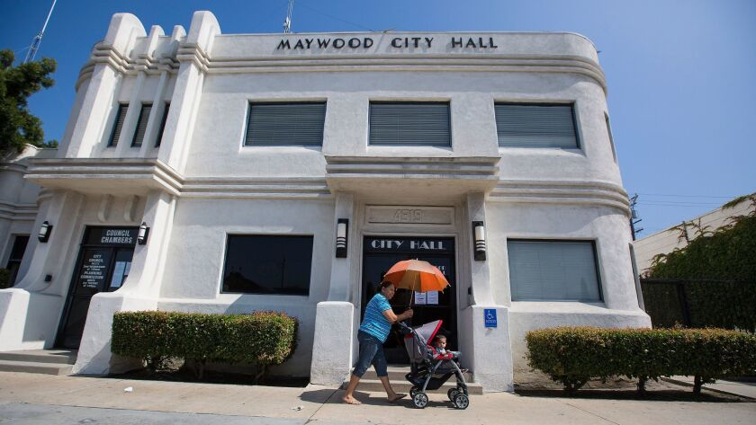 MAYWOOD, CALIF. -- THURSDAY, MAY 12, 2016: A woman pushes a toddler in a stroller past city hall in