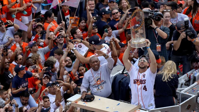 Houston Astros right fielder George Springer (4) holds up the World Series trophy as Houston Mayor S