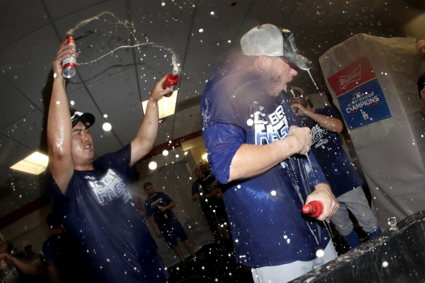 Los Angeles Dodgers pitcher Hyun-Jin Ryu, left, douses center fielder Cody Bellinger during celebration after defeating the Baltimore Orioles 7-3 during a baseball game, Tuesday, Sept. 10, 2019, in Baltimore. The Dodgers clinched the National League West Division title with the win. (AP Photo/Julio Cortez)