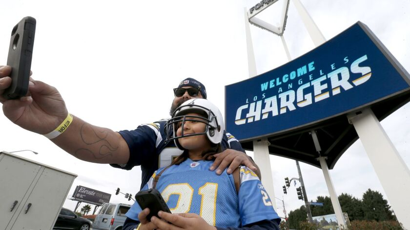 "Chargers fans Luis Salas and his daughter Lily Salas, 9, take a photo together in front of a ""welcome Los Angeles Chargers"" sign at the Forum following a ceremony to kick off Chargers football coming to Los Angeles."