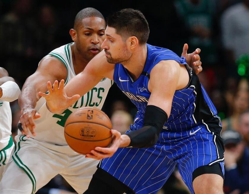 Nikola Vucevic (d) de Orlando Magic en acción ante Al Horford (i) de Boston Celtics hoy, lunes 22 de octubre de 2018, durante un partido de NBA entre Orlando Magic y Boston Celtics, en el TD Garden de Boston, en Massachusetts (EE.UU.). EFE