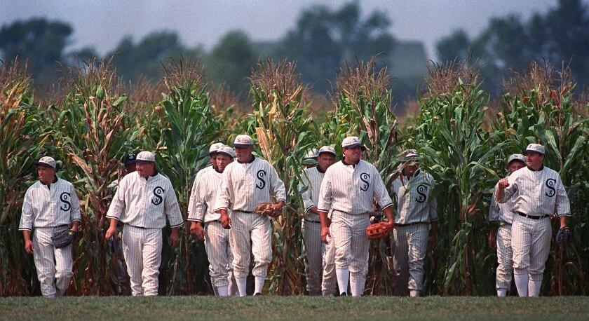 Men in baseball uniforms emerge from a cornfield