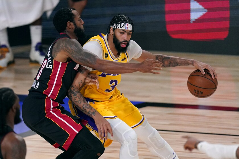 Lakers' Anthony Davis is covered by Miami Heat's Andre Iguodala as he rolls to the hoop.
