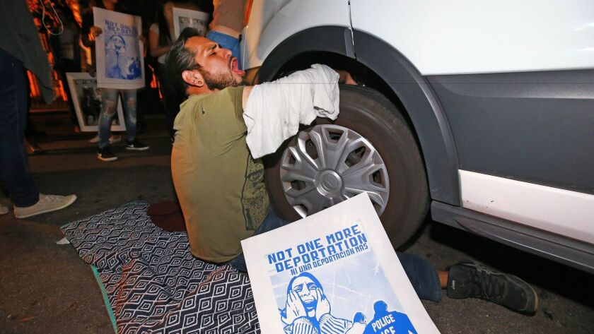 A protester locked himself to the van carrying Guadalupe Garcia de Rayos outside the Immigration and Customs Enforcement field office in Phoenix on Wednesday night.