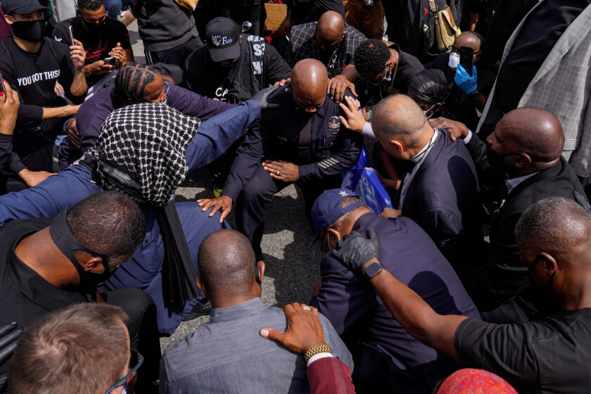 LAPD Commander Gerald Woodyard takes a knee with protesters and clergy members